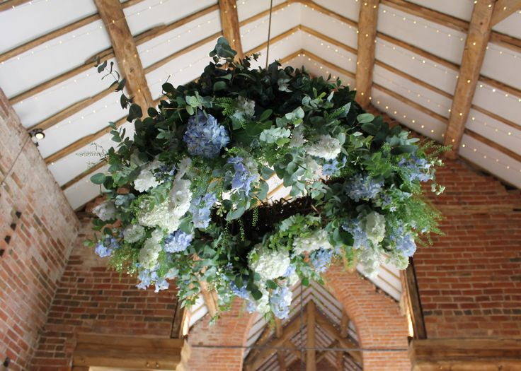 floral wreath hanging from pulley at shustoke farm barns- ivory and blue flowers - delphinium, rose, hydrangeas, eucalyptus