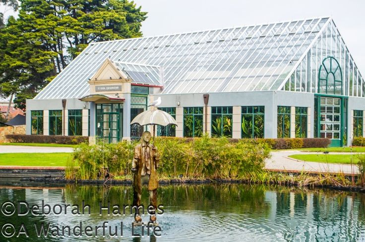 Sculpture of a man with an umbrella (with a seagull on top!) walks across the water in the St. Kilda Botanical Gardens in Melbourne, Australia.