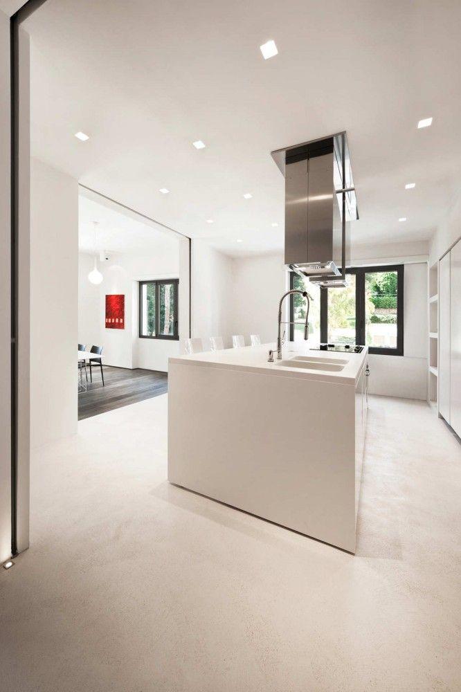 #reforma #cocina con isla central para fregadero y placa de cocción, módulo empotrado, paredes abiertas con puertas correderas, suelo de microcemento.
