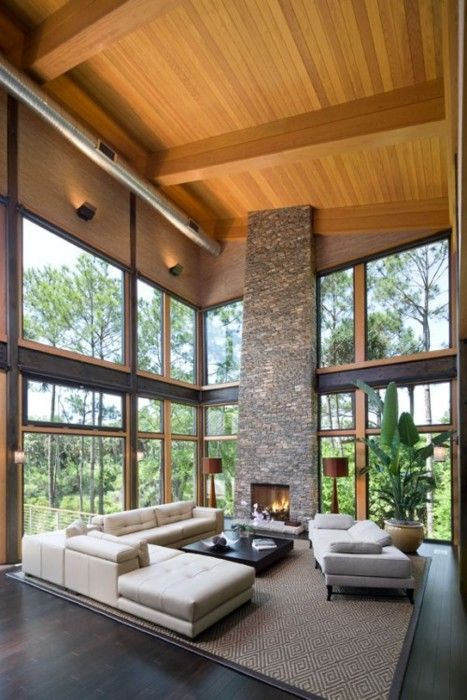 A dramatic room with an abundance of tall windows and a floor to ceiling stone fireplace
