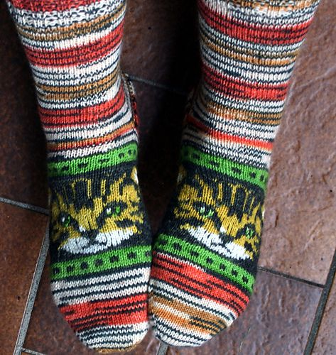 """Ravelry: Stubentiger - tabby cat pattern by Beate Zäch Sock pattern knitted toe up with heel flap. Stranded knitting for the cat, plain stockinette at heel and leg. Cat's chart is given for 64 and alternative for 68 stitches in the round. Pattern comes in 3 languages. Please choose file """"tabbycatsocks"""" for English."""