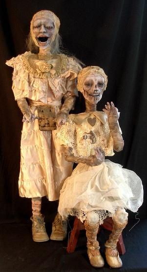 Poor sisters Aurora and Venus were found in a Philadelphia attic.  The girl's beauty can still be seen through the decay. Antique clothing and wrappings were used to create them.