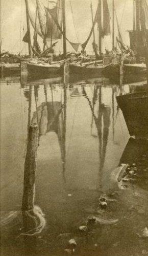 De haven van Volendam met zeilen en netten van de vissersboten weerspiegeld in het water. Volendam, zonder jaar.