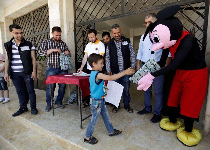 Μία διαφορετική σχολική ημέρα στην Συρία | Ενας άντρας ντυμένος Μίκι Μάους δίνει απολυτήρια αλλά και δώρα στους μικρούς που αποφοίτησαν από σχολείο στην περιοχή Maaret al-Numan που ελέγχεται από τους αντάρτες REUTERS/Khalil Ashawi