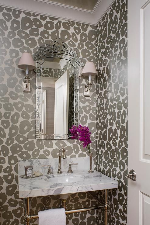 Gray, glam powder room features walls clad in gray leopard print wallpaper lined with a 2 leg marble washstand and a venetian mirror.