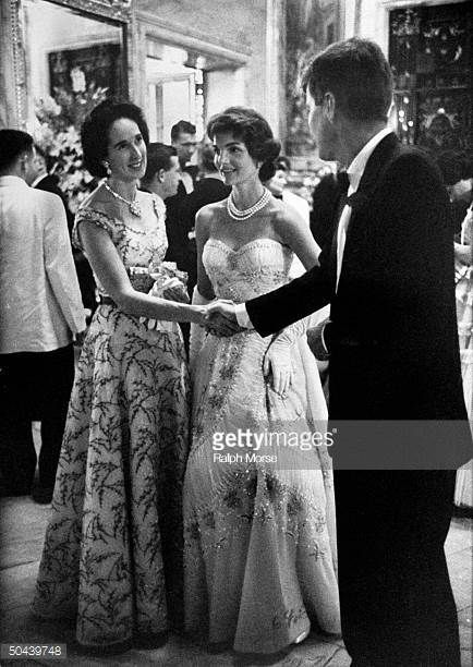 Sen John Kennedy shaking hands w socialite Mrs John Drexel III as his wife Jacqueline pregnant w daughter Caroline clad in beaded shirred white...