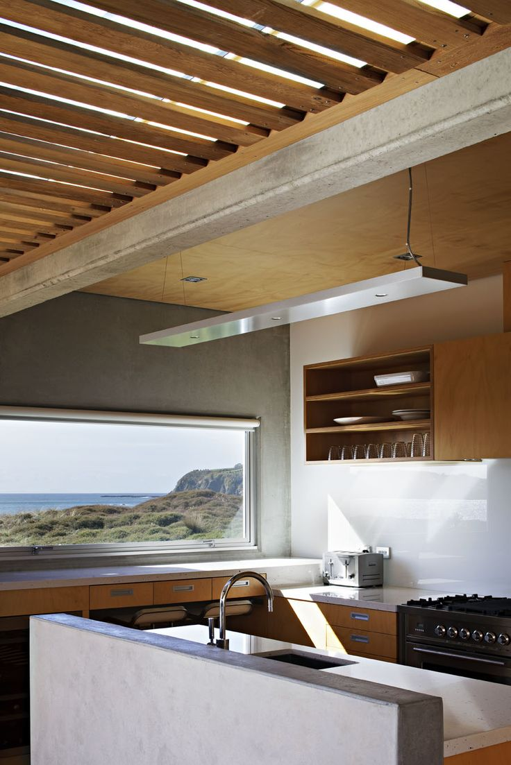 Simple minimalist modern wood and steel kitchen with an amazing view of the mountains and water, imagine cooking here!