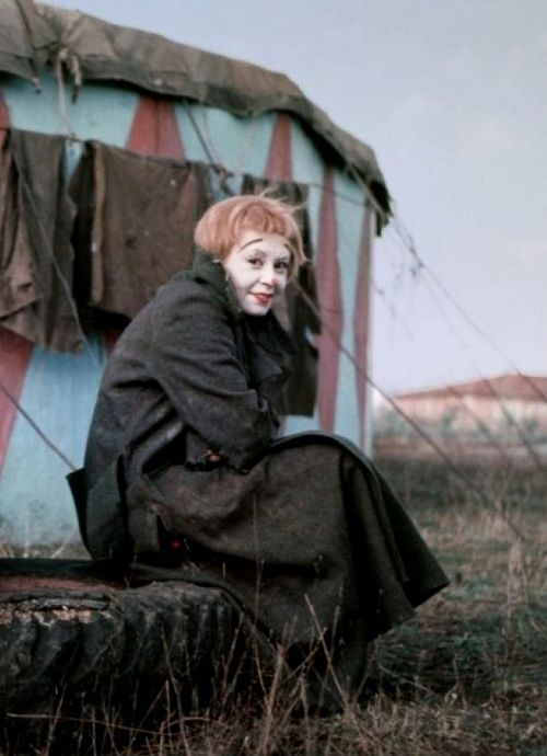 "Giulietta Masina on the set of La Strada (1954, dir. Federico Fellini) (via)  ""Mr. Fellini says that his wife sometime resists his view of her talents, which he summarizes as 'a mingling of youngish and clownish.' But make no mistake: in suggesting that his wife is a clown, Mr. Fellini means no insult. 'The clown is the aristocracy of acting,' he says. 'To be a clown means to have the possibility of making people cry and laugh.'"""