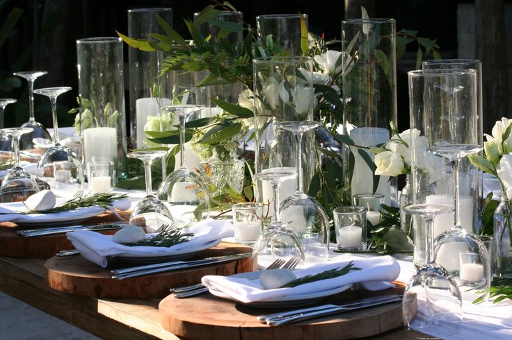 CBC310 Weddings Riviera Maya centerpiece mix of glass containers, greenery and white floral / centro de mesa con follajes y flores en botellas   The Tablescape