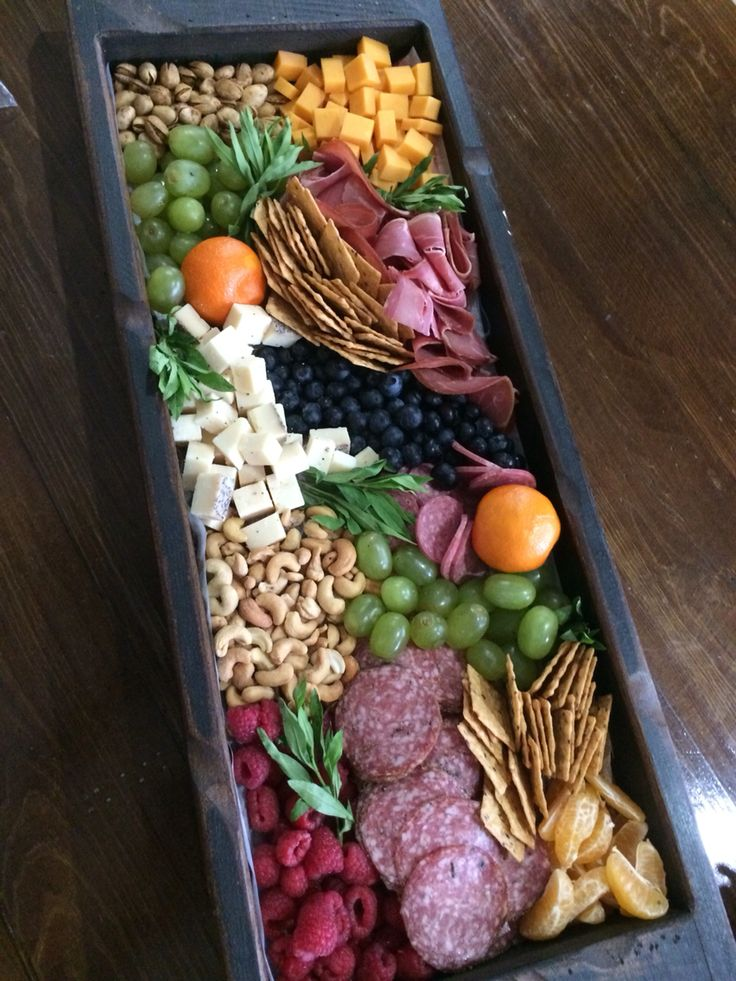 Beautiful, edible table centerpiece! Consists of prosciutto, peppered salami, cashews, pistachios, grapes, raspberries, mandarins, blueberries, crackers and two different cheeses.