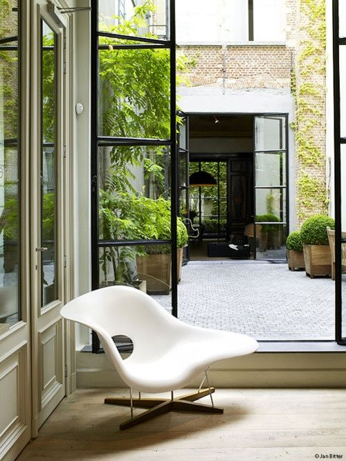 La Chaise de Eames y puertas de cristal y marco de hierro negro abiertas al jardín | Eames La Chaise and black metal framed glass doors opening to the garden · ChicDecó