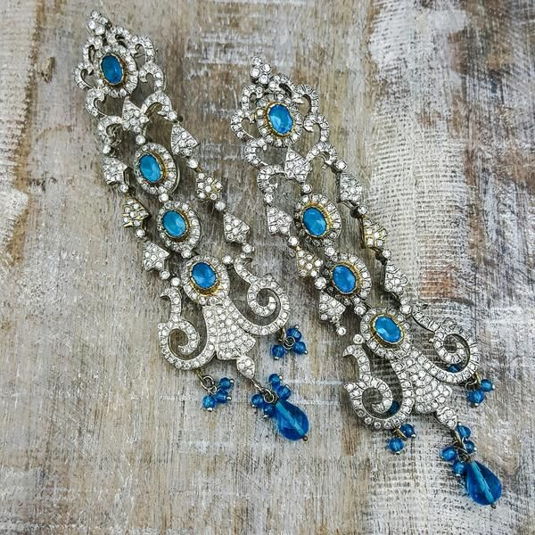 Faye - These chandelier earrings look outstanding being covered with clear cubic zirconium stones and blue stone accents for fancifulness!