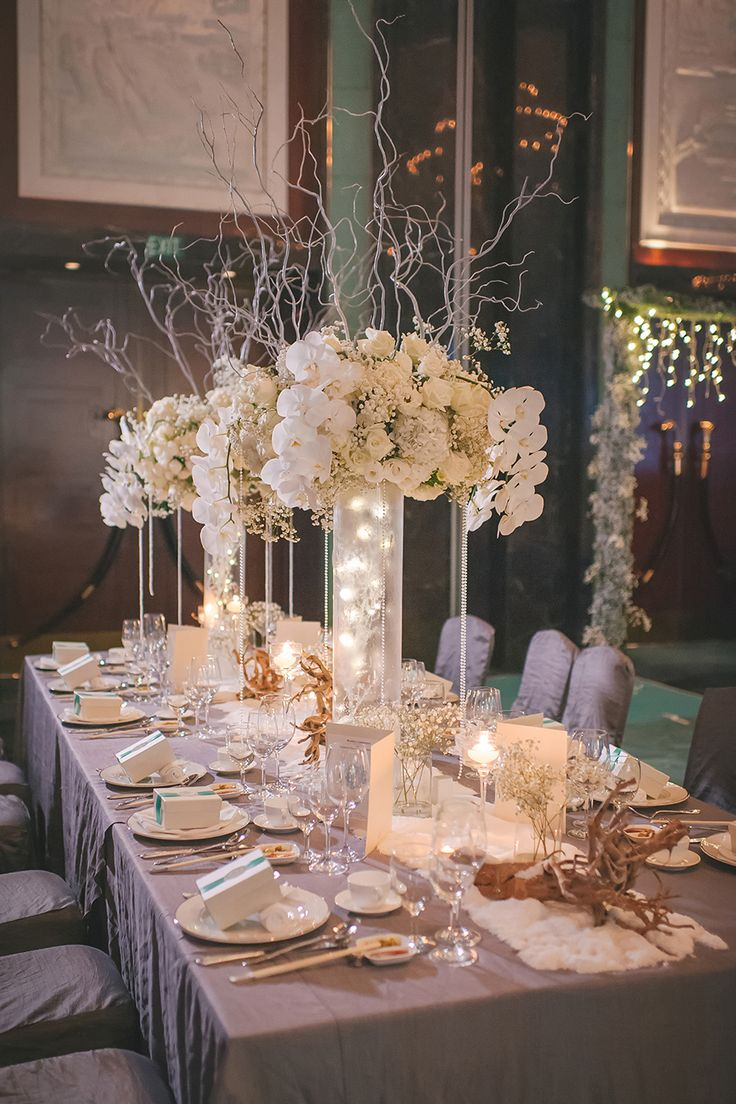 Tall table flower arrangements with white orchids // Desmond and Charlotte's Winter Wonderland Wedding at Shangri-La Hotel