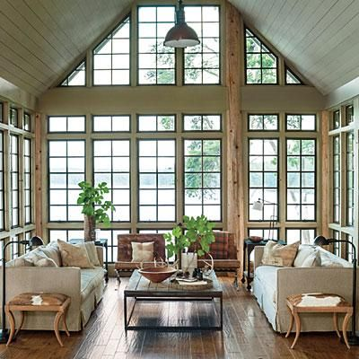 Focus on the View | A neutral palette devoid of area rugs or window treatments camouflage this lake house living room with its surroundings. | SouthernLiving.com