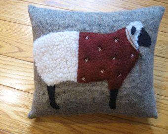 Celui-ci est un autre pour les amateurs de mouton! J'ai conçu celui-ci moi-même et il mouton dispose de deux fait dans le thé teinté en feutre avec les jambes et le visage noir de laine. La maman est tenant une couronne brodée et le plus petit mouton porte son chapeau de Noël complet avec grelot fourrure en garniture et rouillé.  Ce coussin est entièrement cousu à la main et se fait sur une laine de couleur marron moyen. J'ai il bourré d'ouate de polyester. Il mesure 9 1/2 x 12 1/2 et…