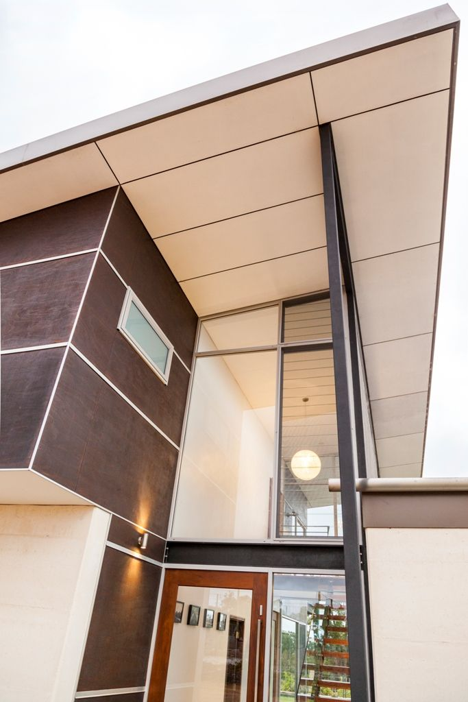 ENTRY - Breezeway glass louvres to underside of eaves lining to capture cooling breezes with exposed structural steel with maceous iron oxide finish.