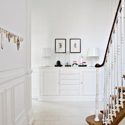 Hall & staircase of jewelry designer Sandrine Zigler-Munck's house. Collection of trinkets from her travels on the wall.