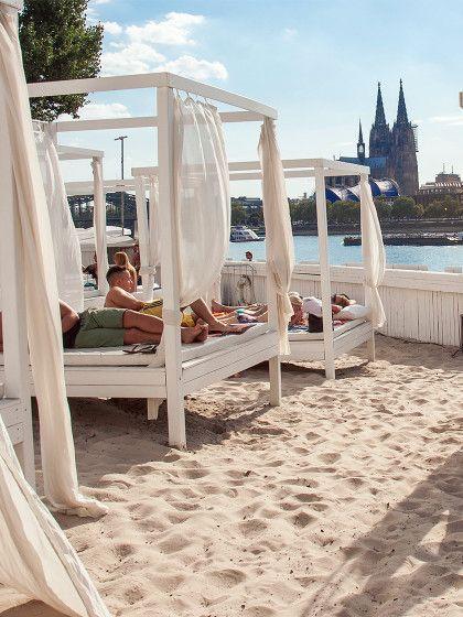 """Beach-Feeling mitten in der City: Die coolsten Stadtstrände in Deutschland. Hier der """"Km 689 Cologne Beach Club"""" in Köln. FeinerSand, weiße Strandbetten, Blick auf's Wasser... Fast könnte man meinen,man sei auf Ibiza."""
