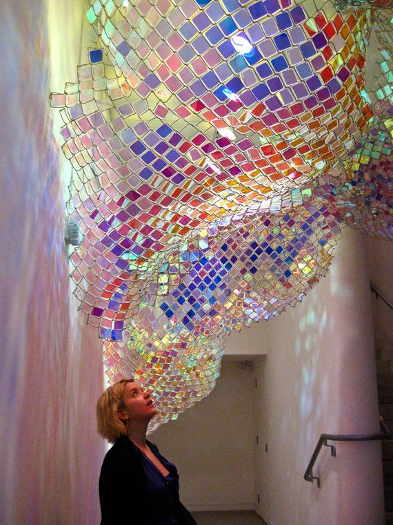 """Capturing Resonance"" exhibit at the deCordova Museum (MA).Sculptor Soo Sunny Park and composer Spencer Topel. Park inserted thousands of acrylic squares into chain link fencing, making the piece a constantly evolving palette of colour, shadows, and reflection. The installation also features Topel's audio element, activated by motion sensors so the sound is ever-changing and layered like its iridescent muse."