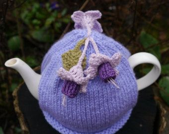 A pretty coral rosebud sits on a cream ribbed mug cosy. The rose is hand knitted with a dark green stem. There is a wooden button for fastening around the mug. Made with good quality wool and cotton. It would make a lovely gift for valentines day. Will fit a standard builders style mug and measures approx 8cm in height. There are other colours available in my shop (please see photos). Hand wash only. Wooden buttons may vary. Mug not included.