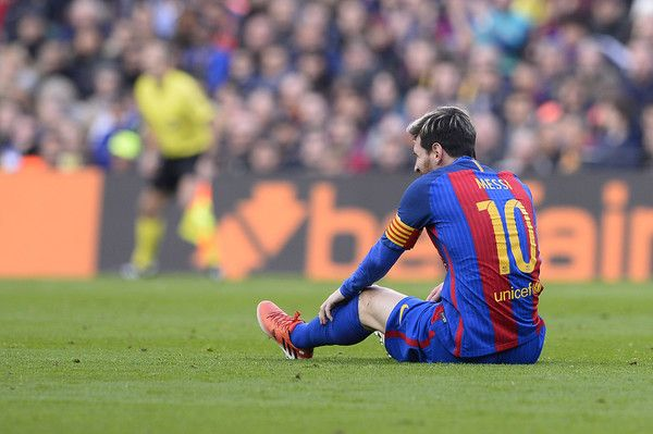 Barcelona's Argentinian forward Lionel Messi sits on the pitch after a fall during the Spanish league football match FC Barcelona vs Real Madrid CF at the Camp Nou stadium in Barcelona on December 3, 2016. / AFP / JOSEP LAGO