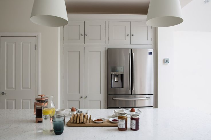 Sustainable Kitchens - Bright Open Plan Family Kitchen in London. Oak shaker style kitchen painted in Farrow & Ball Ammonite. Visible from the Bianco Fantasia worktop with hanging pendant lights is the American style fridge freezer with a closed larder pantry cupboard and storage above.