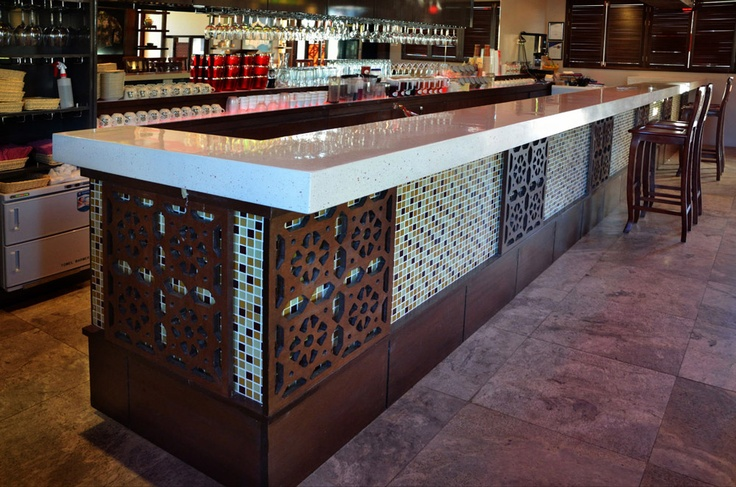 A fully customised concrete bartop. White concrete with white stone and red glass.