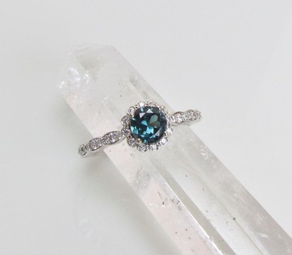 Beautiful, very clean, 5.6mm round, 0.80ct, blue green (teal) sapphire  Ring mount: 14k white gold set with 1/4ct tw GH SI diamonds    Ring size