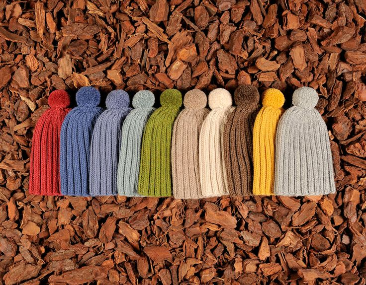 Knitted children's beanies in various colors with yarn tassels. Natural materials and handmade in Denmark.