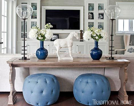 Love those blue poufs tucked underneath a sofa table on on-the-fly seating! - Traditional Home® / Photo: Michael Garland / Design: Lonni Paul