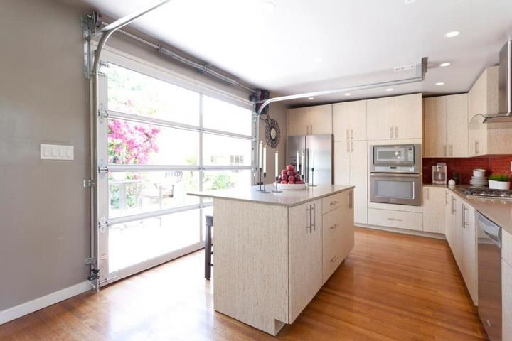 If you really want to open up your kitchen, install a glass garage door instead of a traditional door. This ETO Doors customer let in tons of natural light and created a unique living space.