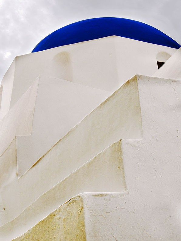 White church with blue dome in Ios island.