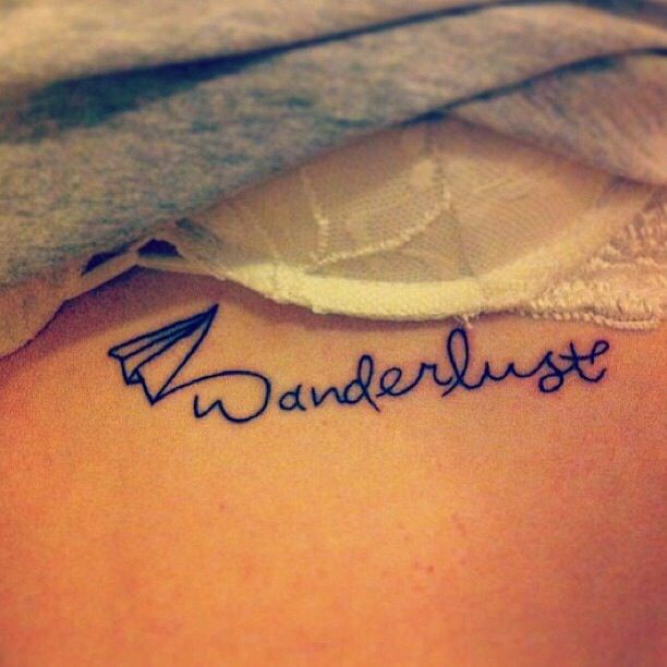 """Wanderlust"" tattooed under her left breast. 