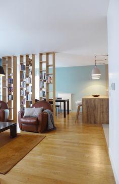 Un salon séparé de sa salle à manger par une bibliothèque et de la cuisine par un bar.