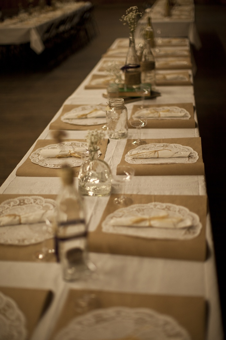 the table settings: brown paper rectangles with glued-on doilies, plastic champagne glasses, plastic silverware wrapped in napkins and old bottles decorated with burlap, ribbon and baby's breath.... cost=cheap!