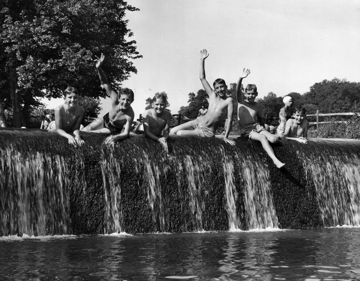 23 Vintage Photos That Show What Summer Fun Looked Like Before The Internet --- Circa 1955: A group of boys in swimsuits wave from atop a manmade waterfall. (Photo by Lambert/Getty Images)