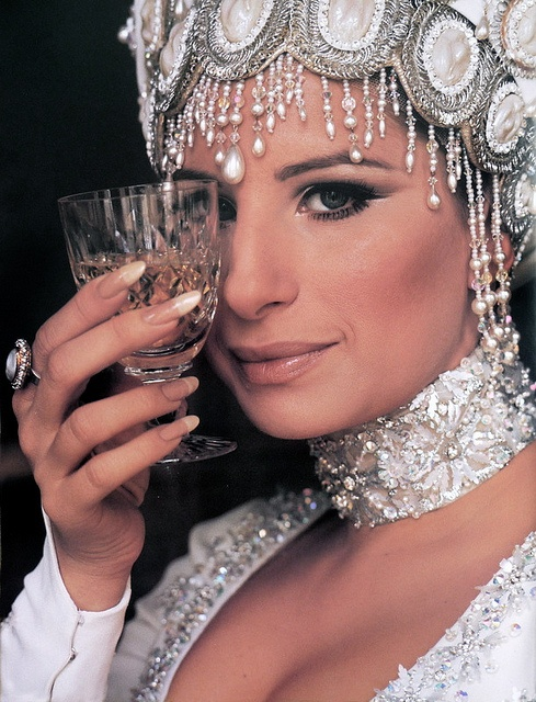 Melinda / Barbara Streisand. Her makeup. Head accessory, neck accessory ( necklace/ neck cuff ), ring, nails. Dress. Not to forget showing off her drink.