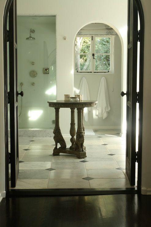 Nate Berkus Design - bathroom with Carrara marble floor with black diamond- elegant bathroom, arched doorway, arched water closet, glass shower, rain shower head, black doors, black bathroom doors, lion table, lion base table, arched water closet doorway,