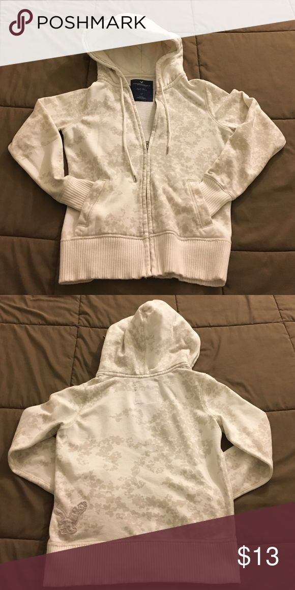 White/cream American Eagle zip up sweater White and cream zip up hoodie from American Eagle. Has a cherry blossom design with the signature eagle patch on the side. American Eagle Outfitters Jackets & Coats