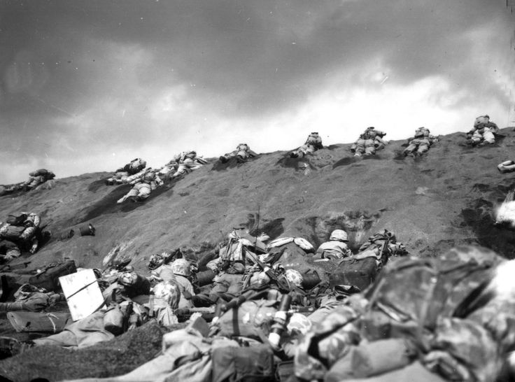 U.S. Marines of the 5th Division inch their way up a sand dune on Red Beach No. 1 toward Mount Suribachi, as the smoke of the battle drifts over them during the initial invasion on Iwo Jima, on February, 19, 1945.