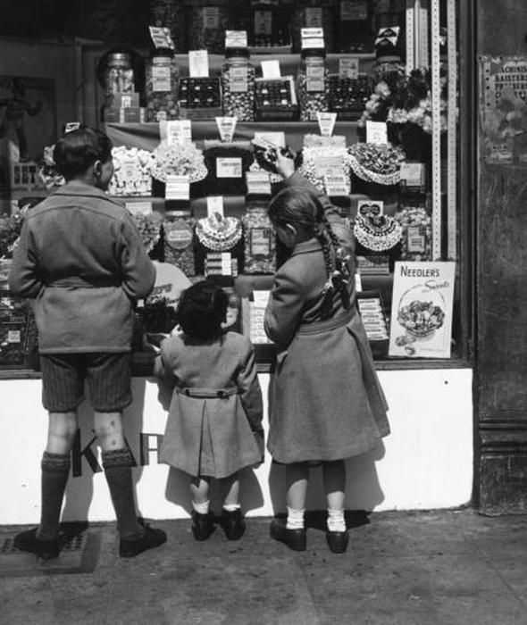 Children admiring the display in a sweetshop window, as WW2 rationing ends in the United Kingdom.