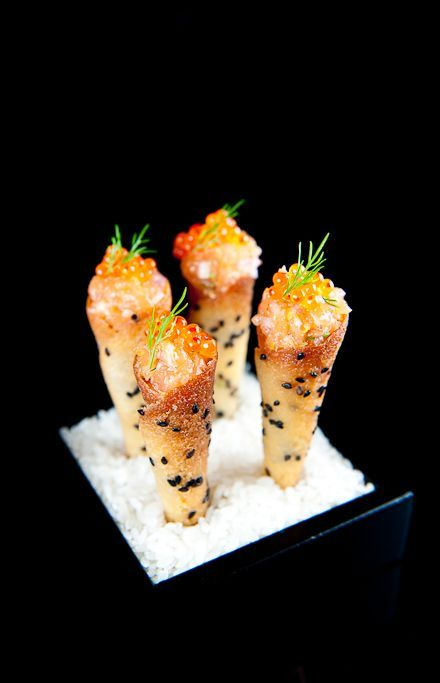 salmon tartare with sweet red onion crème fraîche cornets in black sesame tuile. tuile: flour, sugar, salt, butter, egg whites, and black sesame seeds. salmon tartare: salmon, olive oil, lemon zest, chives, shallots, salt and white pepper, salmon roe, and dill. crème fraîche: red onions, crème fraîche, and salt and white pepper.