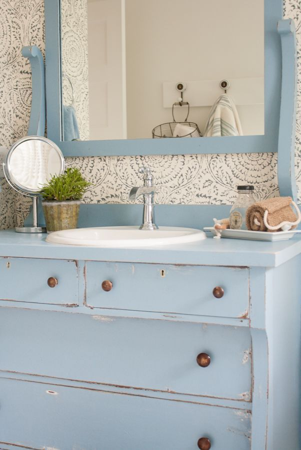 Blue and white bathroom featuring Anthropologie floral wallpaper, a vintage dresser turned bathroom vanity and white penny tile floors.