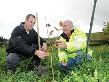 Tree planters needed in Barrie - Kevin Rankin, left, urban forester for the City of Barrie, and Sandy Coulter, right, manager environmental operations, examine a maple tree planted near the Sandy Hollow Landfill site.