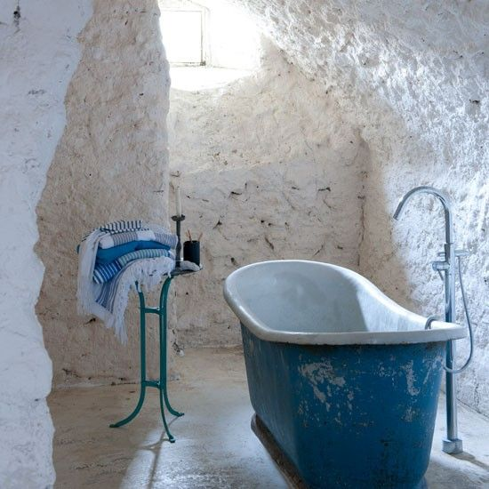 A stack of boldy striped bath towels adds to the Mediterranean mood of this simple bathroom.