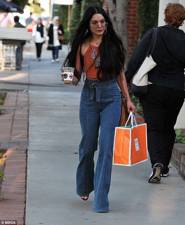 Trendy: The American actress teamed her tiny crop top with stylish high-waisted jeans, which hugged onto the contours of her enviable frame before flaring out