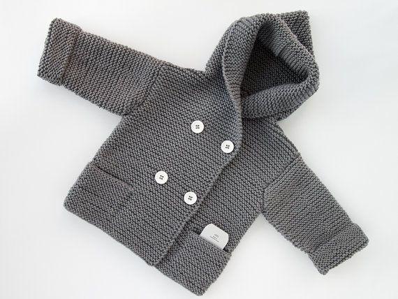 A mano el suéter hecho punto del bebé con capucha con bolsillos laterales y cruzado de botones está hecho de 100% lana merino. Este suéter tiene botones blancos. En los cuadros suéteres son gris, blanco, colores azul marino, oscuros azules y mar verdes. Usted puede elegir colores, tamaño como desee.  ¡Este suéter es muy suave y caliente!  El suéter puede ser pedido en tallas 0-3 meses, 3-6, 6-9 meses, 9-12 meses, 12-18 meses 18-24 meses.  El suéter es tejido a mano y hecho a pedido y tarda…