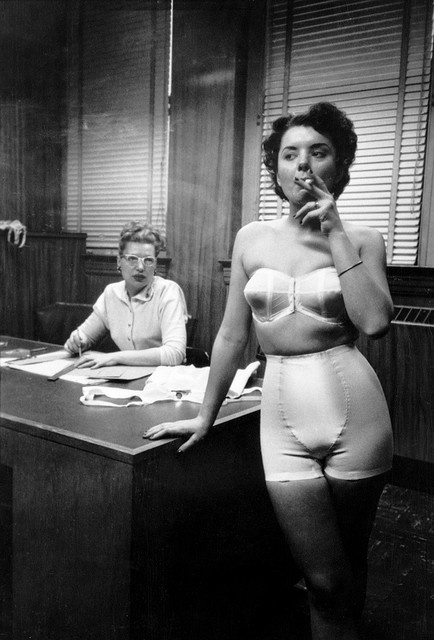 Lingerie model smoking in an office, Chicago, 1949. Photo by Stanley Kubrick