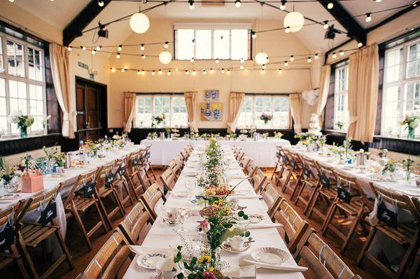 Colourful Homemade Village Hall Wedding Festoon Lights Long Tables http://hollydeacondesign.com/