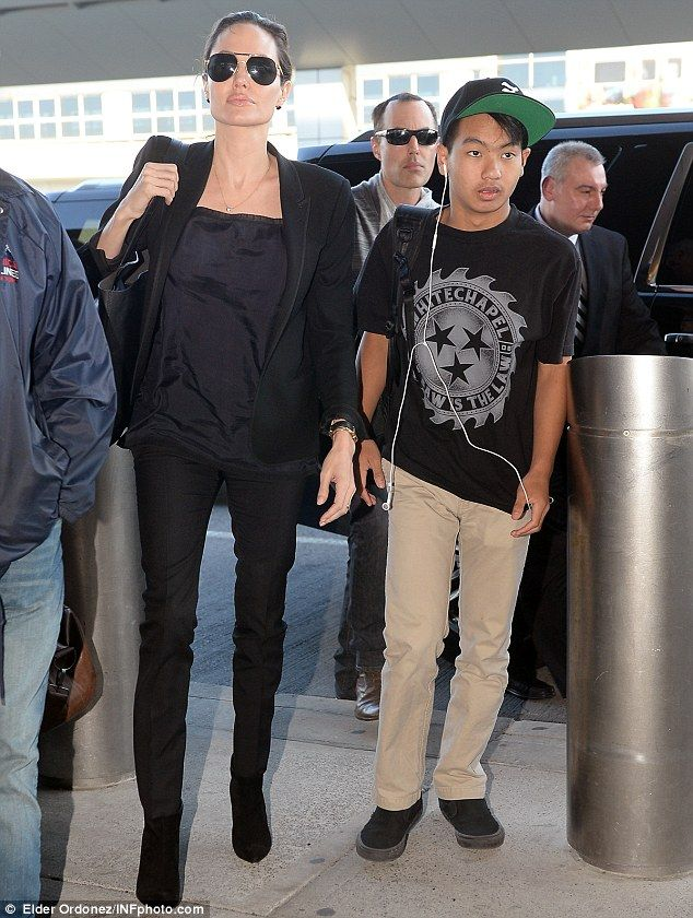 Travel style: Angelina kept it simple in a black blouse and black skinny jeans...